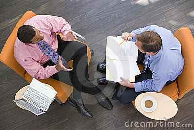 Two businessmen sitting indoors having a meeting