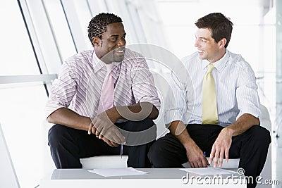 Two businessmen sitting in office lobby talking