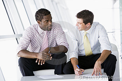Two businessmen sitting in office lobby talking