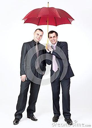 Two businessmen standing under an umbrella