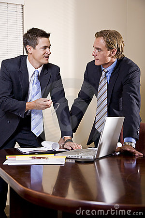 Two businessmen in suits working in boardroom