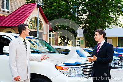 Two businessmen talking about cars