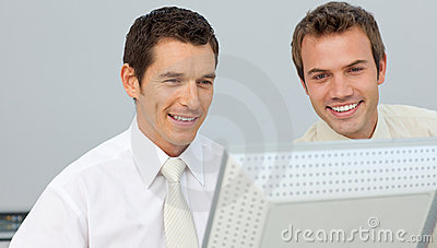 Two businessmen working together at a computer