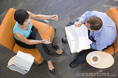 Two businesspeople sitting indoors having meeting