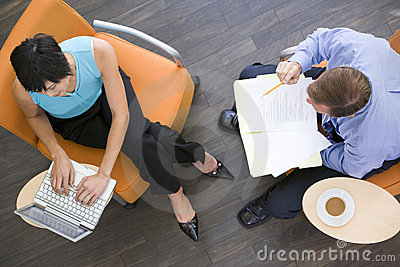 Two businesspeople sitting indoors having meeting