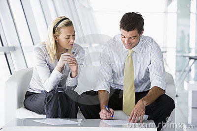 Two businesspeople sitting in office lobby talking