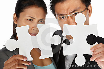 Two businesspeople trying to connect the puzzle