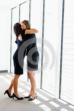 Two Businesswomen Hugging In Office