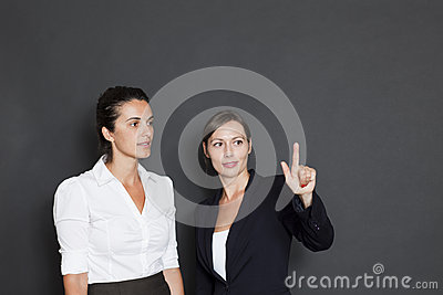 Two businesswomen pointing on a virtual screen