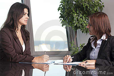 Two businesswomen sitting at office desk