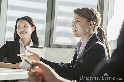 Two businesswomen smiling, discussing, and gesturing during a business meeting