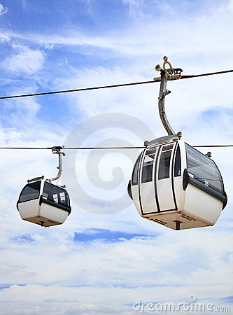 Two cable car on a partly cloudy sky background