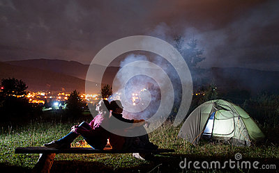 Two campers sitting back to back near tent and campfire Stock Photo