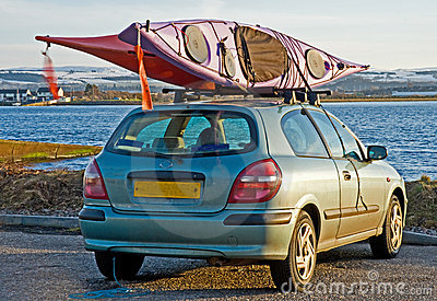 Two canoes fixed on top of a car.