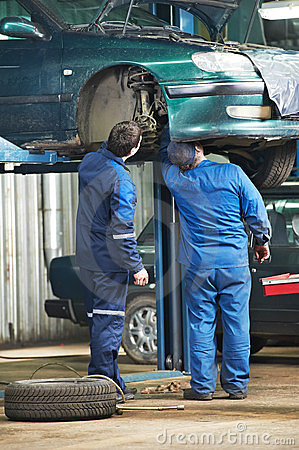 Two car mechanic diagnosing auto suspension