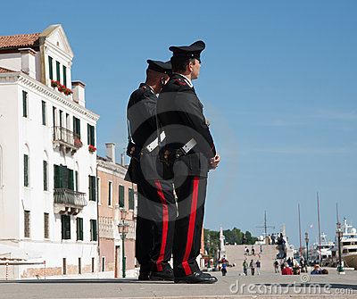 Two carabinieri or police stand obrserving. Editorial Image