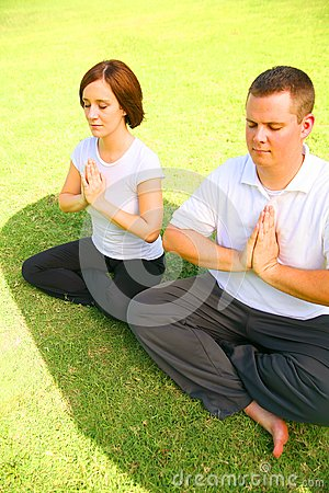 Two Caucasian Meditate On Grass