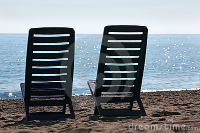 Two chairs stand on beach near sea