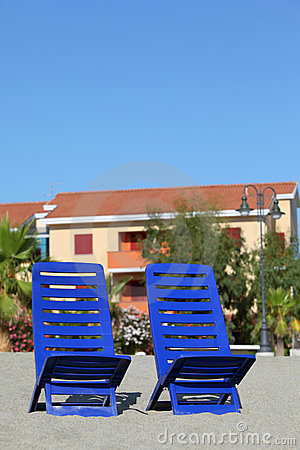 Two chairs stand under sun on beach near cottages