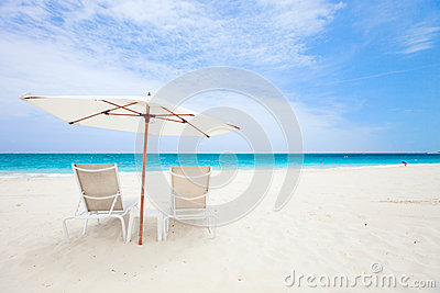 Two chairs under umbrella at beach