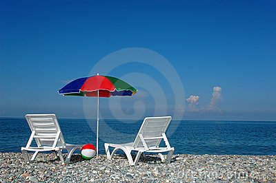 Two chaise lounges and umbrella on a beach