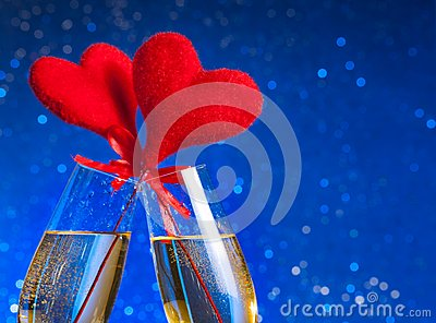 Two champagne flutes with golden bubbles and red velvet hearts make cheers on blue bokeh background