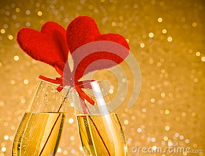Two champagne flutes with golden bubbles and red velvet hearts make cheers on golden bokeh background