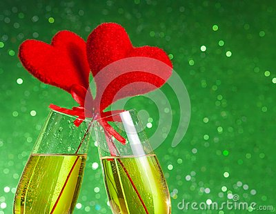Two champagne flutes with golden bubbles and red velvet hearts make cheers on green bokeh background