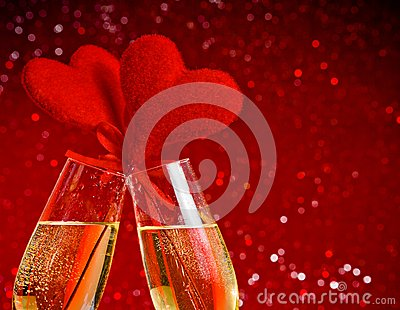 Two champagne flutes with golden bubbles and red velvet hearts make cheers on red bokeh background