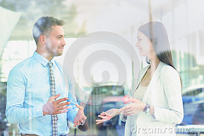 Two cheerful smiling young businesspeople talking at the office