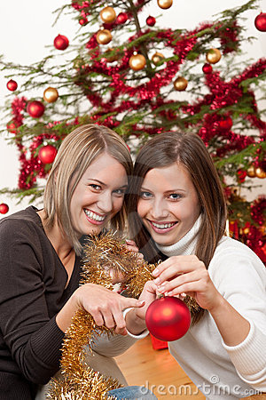 Two cheerful women with Christmas chains and balls