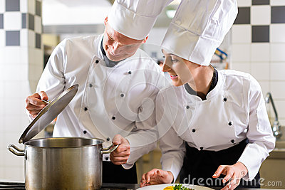 Two chefs in team in hotel or restaurant kitchen