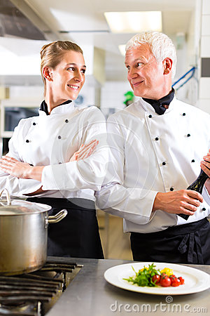 Two chefs in team in hotel or restaurant kitchen