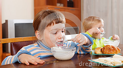 Two  children eating dairy breakfast