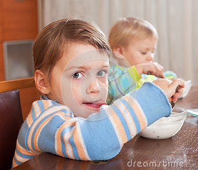 Two  children eating  yogurt
