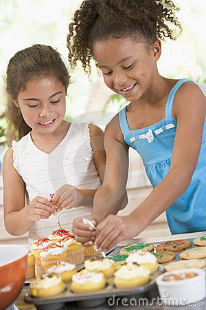 Two children in kitchen decorating cookies