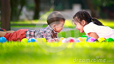 Two children are laying on green grass and smile