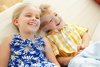 Two Children Lying Upside Down On Sofa At Home