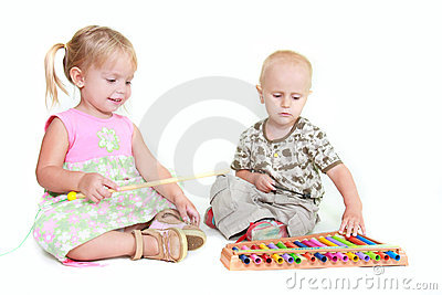 Two children playing music piano