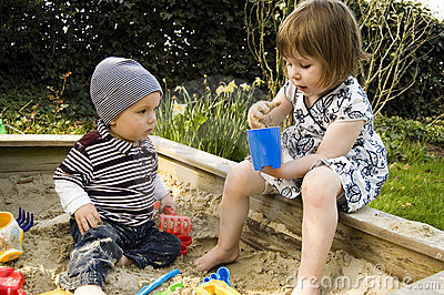 Two Children Playing In A Sandbox