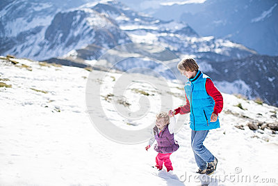 Two children playing in snow in mountains