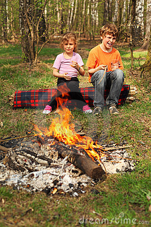 Two children sit near campfire