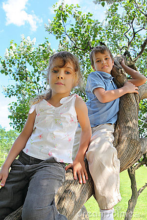Two children sit on thick barrel of lilac