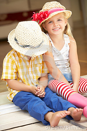 Two Children Sitting Outside House