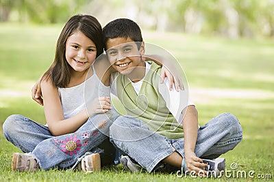 Two children sitting in park