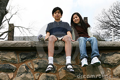 Two children sitting on rock ledge
