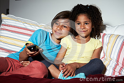 Two Children Sitting On Sofa Watching TV Together