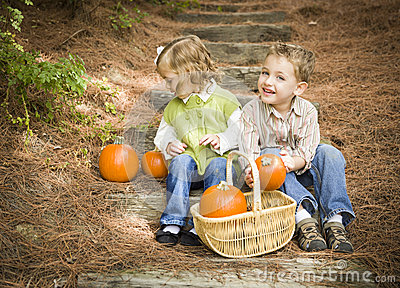 Two Children Sitting on Wood Steps with Pumpkins