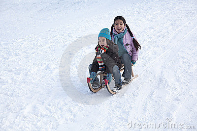 Two children on a sled having fun