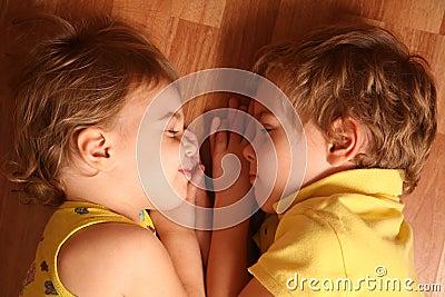 Two children sleep on floor